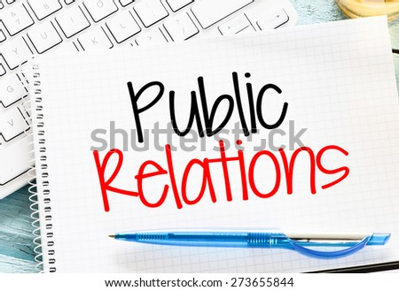 Notepad with public relations and keyboard on wooden background