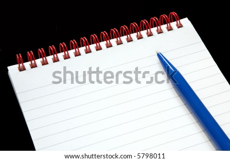 Notepad with red rings and a blue pen on a black background.