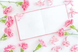 Notepad with space for text and pink flowers on white background. Top view with copy space.