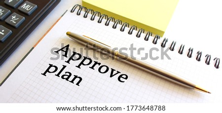Notepad with text APPROVE PLAN on a white background, near calculator and yellow note papers. Business concept.
