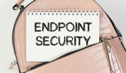 Notepad with text ENDPOINT SECURITY. A notebook peeks out of the pocket of a pink bag.
