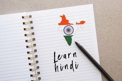notepad with the inscription learn hindi, india flag and country map, pen, foreign language learning concept