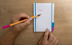 Notepad with white pages with an orange body pen and pink ink on an office desk used for home office. Written in detail mentioning goals being marked with a white woman's hand.