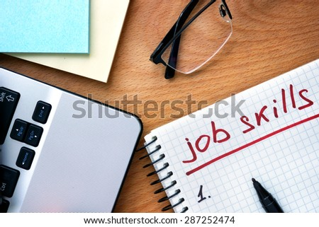 Notepad with words job skills on a wooden background