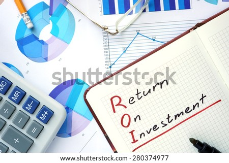 Notepad with words ROI return on investment  concept and marker.
