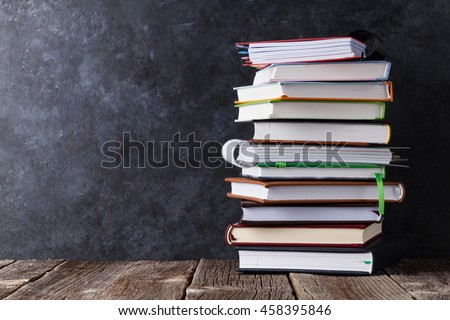 Notepads on table in front of chalk board. Back to school concept with copy space