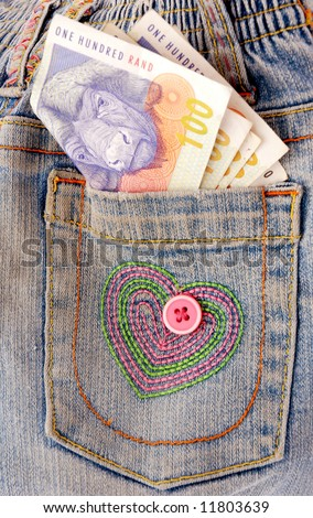 Notes of South African Rand money in the pocket of a kids blue jeans