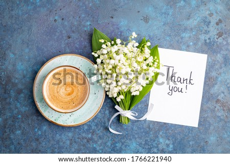 Notes thank you and coffee mug with bouquet of flowers lily of the valley on blue background. Thankfulness, coffee cup, customer service, thanks card concept, top view, flat lay Сток-фото ©