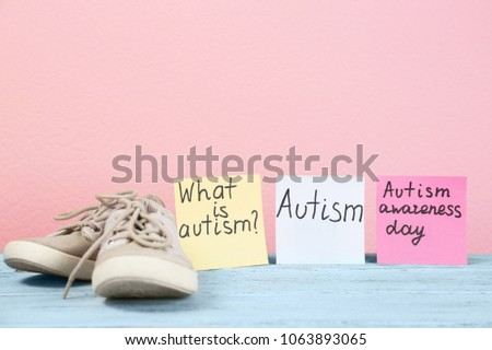 Notes with autism related phrases and child trainers on table #1063893065