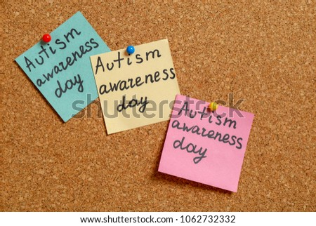"Notes with phrase ""Autism awareness day"" on cork background #1062732332"