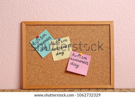 "Notes with phrase ""Autism awareness day"" on cork board against color background #1062732329"