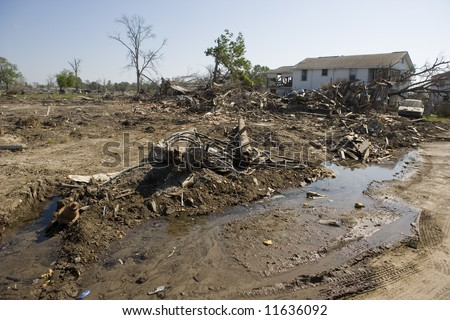 Nothing but a pile of rubble remains of the houses that once occupied lots in the Ninth Ward of New Orleans. Construction continues on the levy broken by the flood waters of Katrina. - stock photo