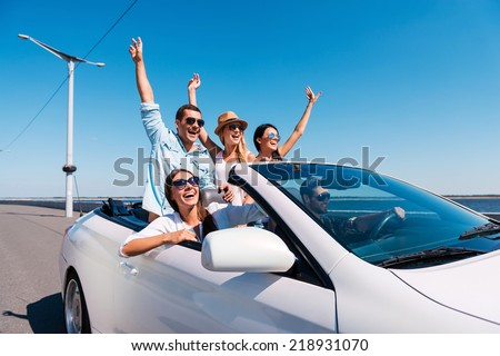 Nothing but friends and road ahead. Group of young happy people enjoying road trip in their white convertible and raising their arms up #218931070