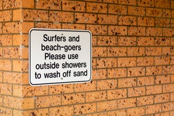 Notice on a brick wall - Surfers and beach-goers please use outside showers to wash off sand