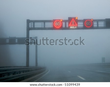 Notification traffic sign on a highway at strong fog