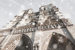 Notre Dame cathedral in Paris, France in gloomy winter day in snowstorm. Upward glance. Pastel trendy toning. Beautiful inspiring moody faded scenery