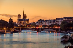 Notre Dame de Paris Cathedral, Ile Saint Louis and the Seine River at sunset. Summer evening with the Sully Bridge and city lights in the 4th Arrondissement of Paris. France