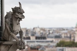 Notre dame Gargoyle sculpture watching over Paris from high up on the cathedral tower.