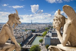 Notre Dame of Paris: Stryge and demon, most famous of all Chimeras, overlooking the skyline of Paris at a summer day (composition)