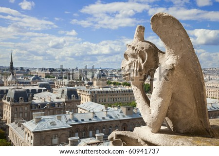 Notre Dame of Paris: The Stryge (most famous of the Chimeres) overlooking the skyline of Paris at a summer day