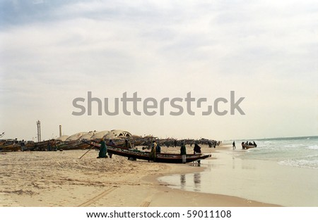 NOUAKCHOTT, MAURITANIA - JAN 5: Local fishermen arrive with their catch at January 5, 2006 in Nouakchott, Mauritania. Fresh fish is sold daily on the beach.