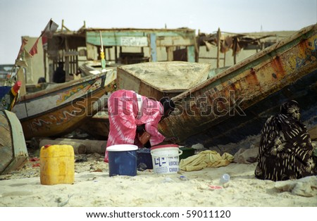 NOUAKCHOTT, MAURITANIA - JAN 5: Local woman cleans fish at the beach at January 5, 2006 in Nouakchott, Mauritania. Fresh fish is sold daily on the beach.