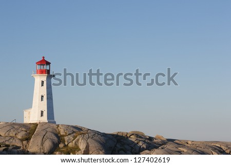Nova Scotia's Peggys Cove lighthouse on a sunny day with blue sky.