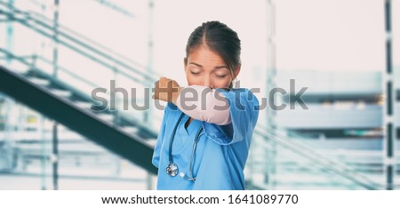 Novel Coronavirus 2019-nCoV Wuhan chinese hospital nurse or Asian doctor woman worker sneezing into arm covering mouth and nose while coughing flu. Virus protection prevention panoramic banner.
