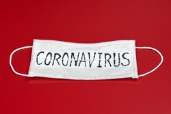 Novel coronavirus - 2019-nCoV, WUHAN virus concept. Surgical mask protective mask with CORONAVIRUS text. Chinese coronavirus COVID-19 outbreak. Red background.
