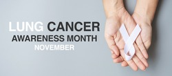 November Lung Cancer Awareness month, .Man holding white Ribbon on grey background