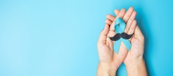 November Prostate Cancer Awareness month, adult Man holding light Blue Ribbon with mustache for supporting people living and illness. Healthcare, International men, Father and World cancer day concept
