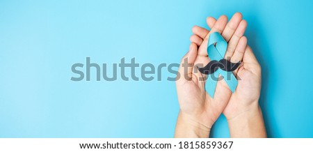 November Prostate Cancer Awareness month, adult Man holding light Blue Ribbon with mustache for supporting people living and illness. Healthcare, International men, Father and World cancer day concept Foto stock ©