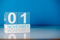 November 1st. Day 1 of last autumn month, calendar on blue background. Empty space for text