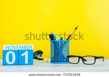 November 1st. Day 1 of month, wooden color calendar on yellow background with office supplies. Autumn time