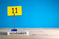 November 11th. Day 11 of november month, calendar on workplace with blue background. Autumn time. Empty space for text