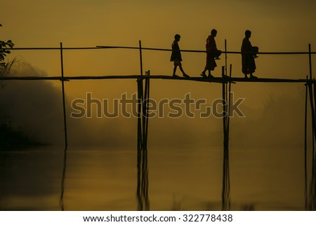 Novice less alms round on a wooden bamboo bridge  at sunrise Silhouette thailand\ monks receive food offering  Thailand. Offering food is one of most common rituals in Buddhism.