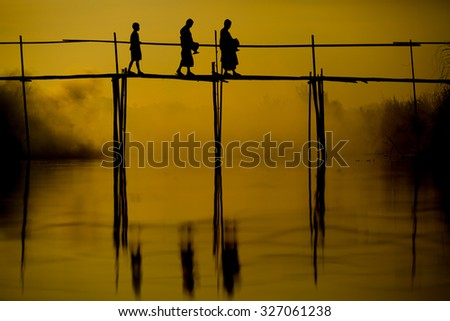 Novice less alms round on a wooden bamboo bridge at sunrise Silhouette thailand monks receive food offering Thailand. Offering food is one of most common rituals in Buddhism.