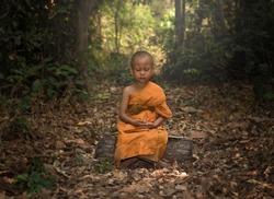 Novice meditating for young buddhist novice monk