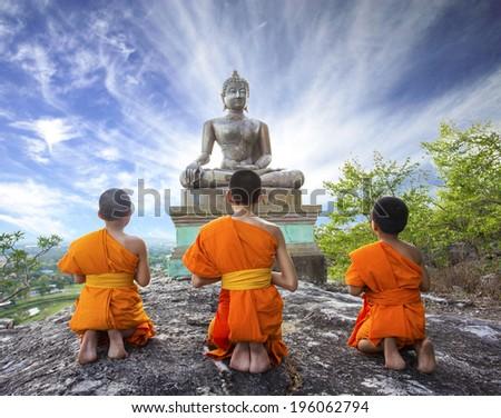 Novice Monk praying to the Buddha in Phrabuddhachay Temple, Saraburi, Thailand.