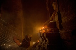 Novice monk praying with candles in front of buddha statue inside old pagoda, Bagan Myanmar