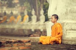 Novices monk vipassana meditation at Ayutthaya Historical Park in Thailand
