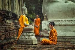 Novices monk vipassana meditation at front of Buddha statue