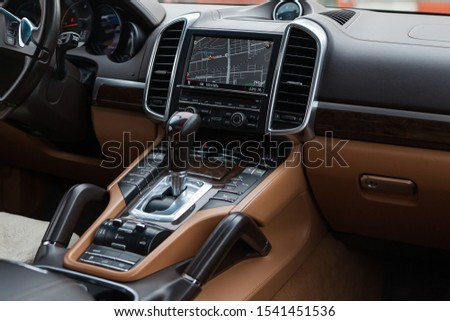 Novosibirsk, Russia - 10.22.2019: The interior of the car Porsche Cayenne Diesel 958 2012 year with a view of the steering wheel, dashboard, seats and multimedia system with light brown leather trim #1541451536