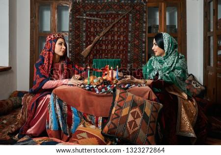 Novruz holiday celebration with Beautiful azeri women and novruz tray with traditional pastry shekerbura and pakhlava food.