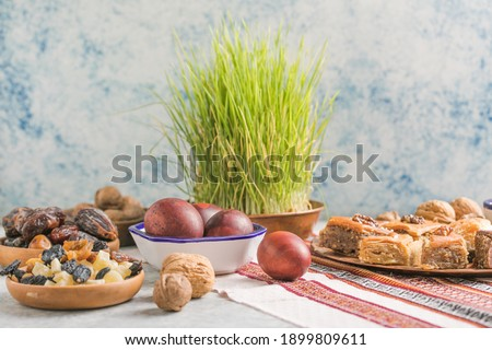 Novruz traditional tray with green wheat grass semeni or sabzi, sweets and dry fruits pakhlava on white background. Spring equinox, Azerbaijan copy space
