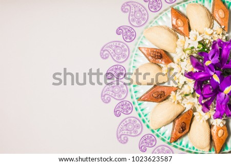Novruz tray plate with Azerbaijan national pastry pakhlava and shekerbura, light grey background decorated with yellow daffodils and purple fleur de lis flowers spring new year celebration copy space