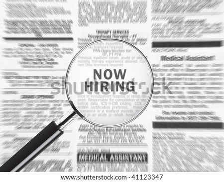 Now hiring ad through a magnifying glass - stock photo