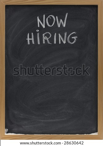 now hiring advertisement handwritten with white chalk on blackboard, copy space below, eraser smudges