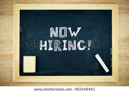 Now hiring!. Blackboard with now hiring! sign, white chalk and duster on wooden background #482648461