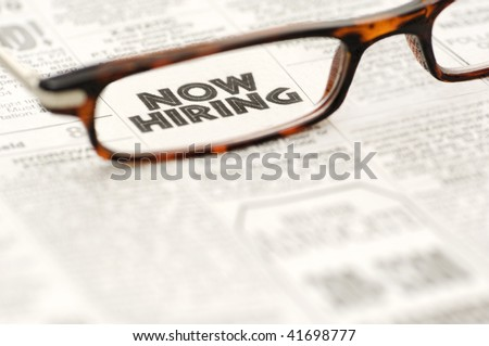 Now Hiring newspaper classified ad framed in a pair of reading glasses.